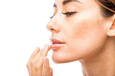 Sexy female model moisturizing her lips against white background