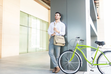 Young male manager contemplating while holding disposable cup by green cycle Standard-Bild