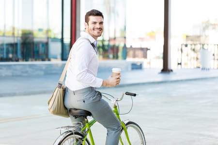 Portrait of administrator smiling while holding disposable cup and riding cycle in city