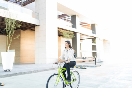 Confident entrepreneur saving environment by traveling on cycle to office