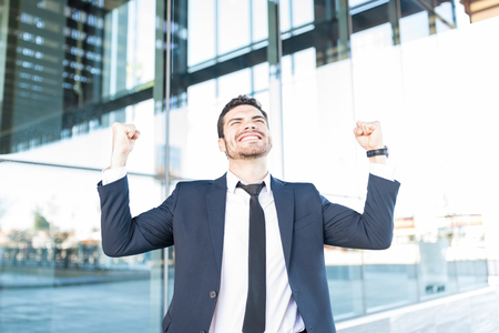 Beau homme d'affaires serrant les poings en triomphe à l'extérieur du bureau moderne