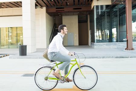 Smart businessman riding bicycle on urban street to work Stock Photo