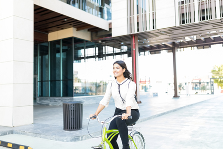 Happy businesswoman looking away while riding bike on city street