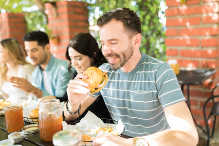 Tempted man in casuals looking at delightful burger at a restaurant