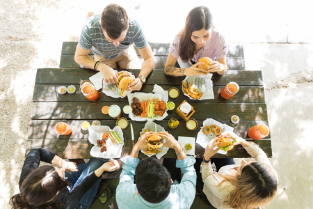 Directly above shot of men and women having junk food at restaurant