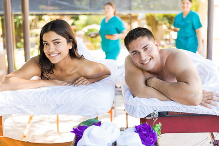 Portrait of smiling young partners lying on massage beds at healthcare center during vacation