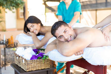 Cropped image of massagers massaging smiling young couple at wellness center Stock Photo