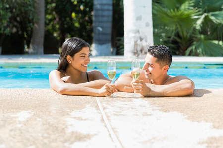 Smiling couple looking at each other while enjoying champagne in swimming pool during summer
