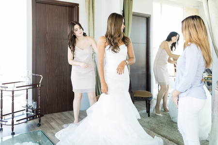 Elegant woman wearing wedding dress while friends looking at her by mirror Stock Photo