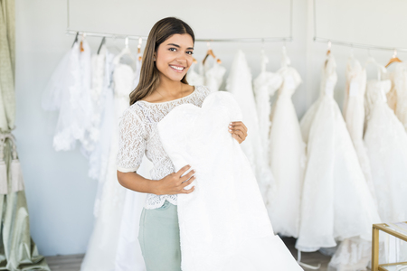 Beautiful portrait of young bride holding her marriage dress while shopping in fashion store