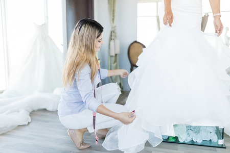 Sales clerk assisting client with ruffles of her wedding dress in fashion studio 免版税图像
