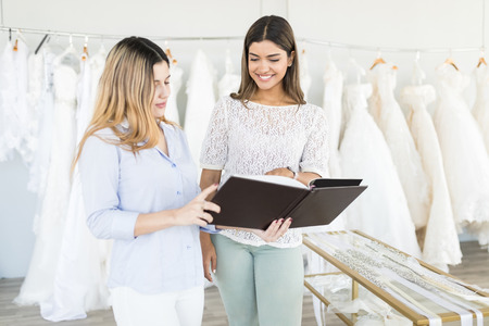 Beautiful saleswoman showing catalog of bridal collection to client in boutique