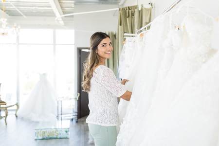 Pretty shopper buying elegant white wedding gown in boutique