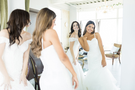 Cute young brides in white dresses looking into mirror at wedding boutique 写真素材