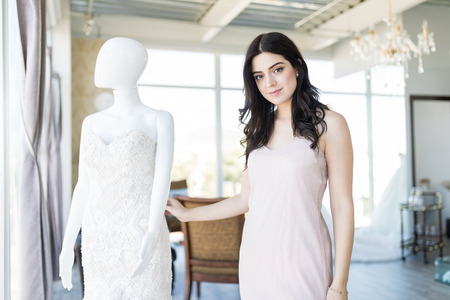 Portrait of an attractive purchaser standing by mannequin in bridal boutique