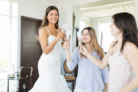 Purchasers finding the perfect wedding gown and celebrating with alcohol in modern boutique