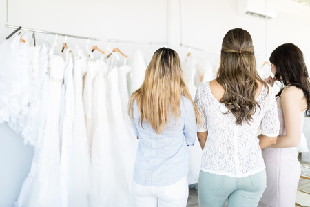 Rear view of confused friends looking at bridal gowns hanging in boutique