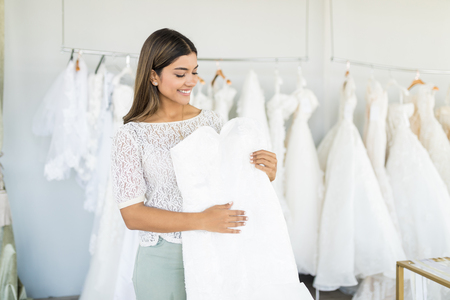Cute Hispanic woman choosing white wedding outfit in bridal shop