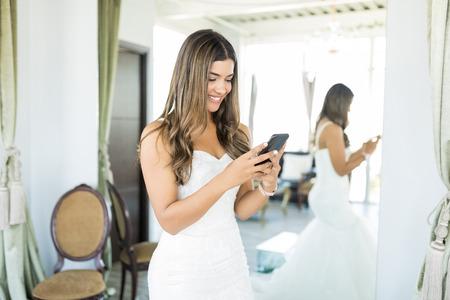 Hispanic customer smiling while using application on mobile phone in bridal studio 写真素材