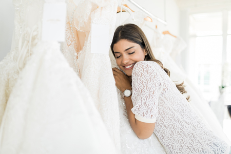 Beautiful Hispanic woman with eyes closed hugging her marriage gown in bridal shop