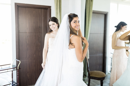 Gorgeous bride in white luxury dress is getting ready for wedding with friend in living room