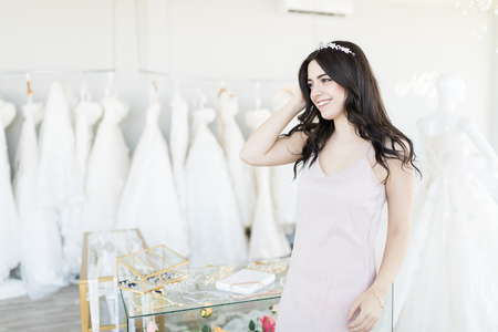 Caucasian bride shopping for wedding accessories in bridal store