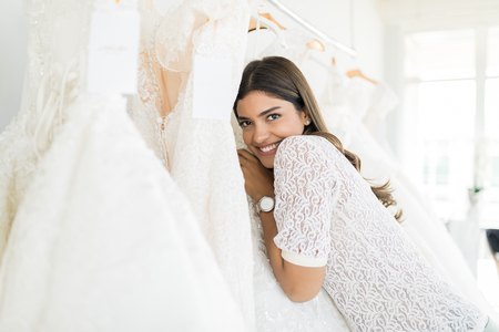 Portrait of smiling young woman embracing her wedding dress at store