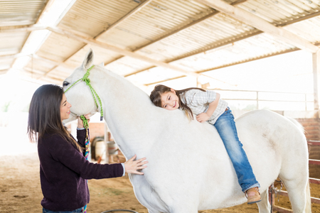 Bareback rider hugging her white horse while mother standing in stable