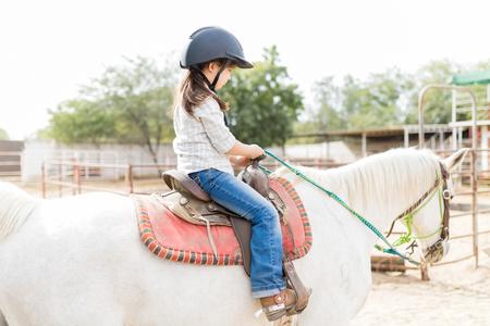 Side view of female child learning horseback riding at ranch Reklamní fotografie
