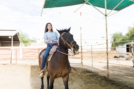 Mid adult woman practicing horseback riding during weekend at ranch