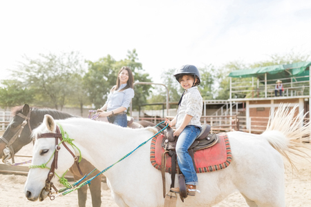 Innocent female child enjoying horseback riding with mother at ranch