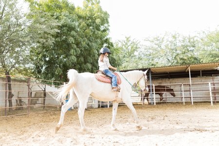 Full length of girl riding horse to learn balance and motor coordination at barn