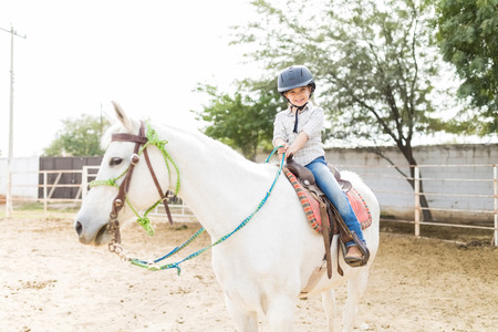 Portrait of excited girl enjoying during Equine-assisted therapy at ranch
