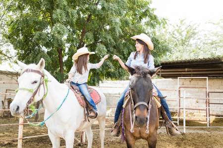 Mother and daughter doing a fist bump while riding brown and white horses at ranch
