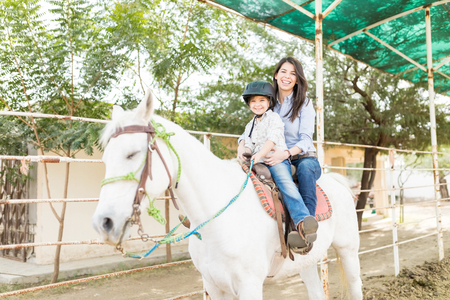 Portrait of happy mother and daughter riding white horse at farm
