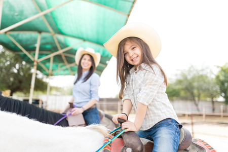 Portrait of happy little girl wearing hat while riding horse with mother in background at ranch