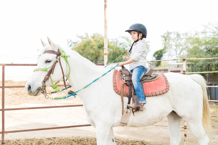 Innocent and cute child enjoying her holiday while sitting on white horse at barn