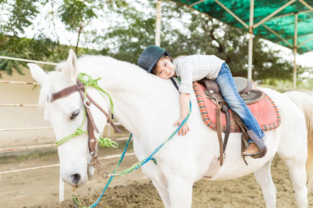 Innocent female rider lying on horse with tenderness at ranch Stock Photo
