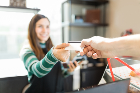 Cropped image of customer giving credit card to cashier in bakery Banco de Imagens