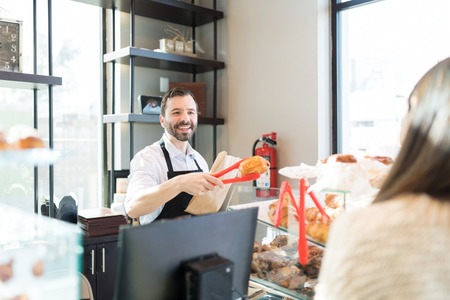 Good looking salesman smiling while packing bread in paper bag for customer at store