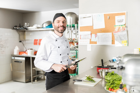 Portrait of mid adult chef sharpening knife in restaurant kitchen Banque d'images