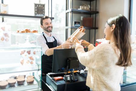 Amichevole proprietario di metà adulto che dà pagnotte di pane fresco alla donna nel negozio di panetteria