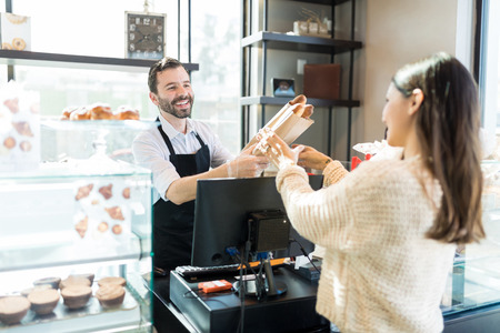 Friendly mid adult owner giving fresh bread loaves to woman in bakery shop Stock Photo