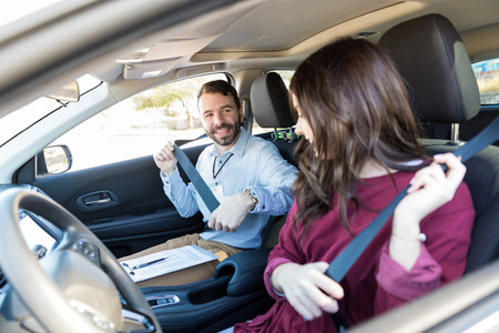 Smiling driving instructor teaching woman to fasten seatbelt of car Stockfoto