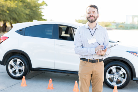 Handsome Hispanic male teacher holding checklist for driving exam