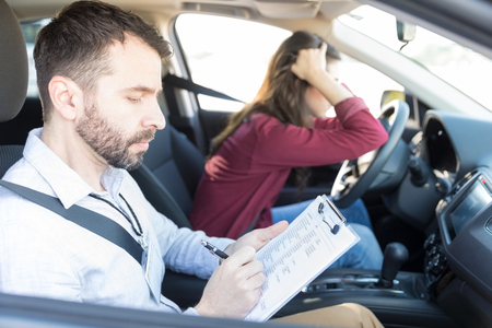 Expert car driving coach giving less marks to sad woman