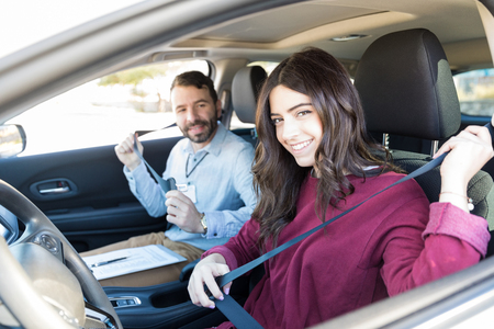 Pretty woman taking life saving driving tips from instructor while sitting in car