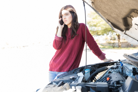 Beautiful woman talking on smartphone while standing near breakdown car in middle of road