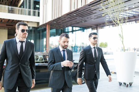 Personal bodyguards in suits protecting president while walking at campus