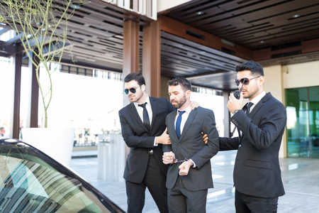 Male secret agents with corrupt politician walking towards car outside office building